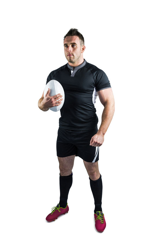 44459336 - tough rugby player holding ball on white background